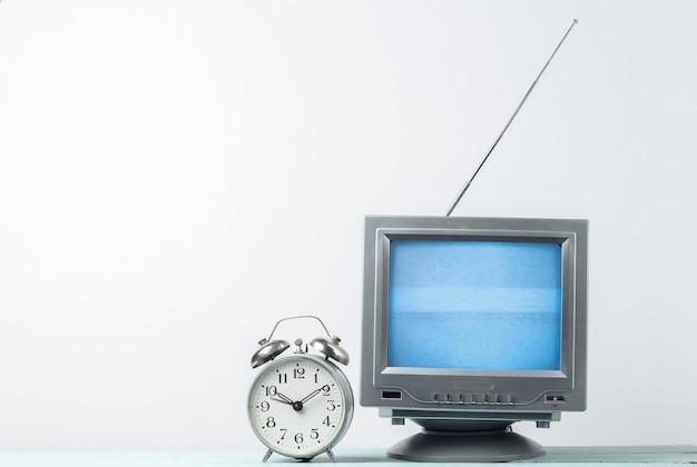 Antenna old-fashioned retro tv receiver and alarm clock on white wall