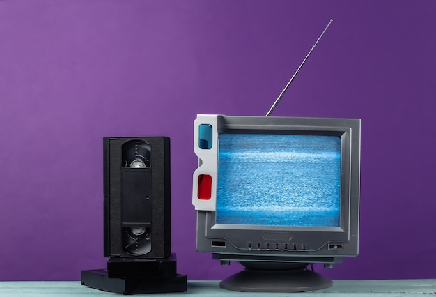 Antenna old-fashioned retro tv receiver, anaglyph 3d glasses and video cassettes on purple