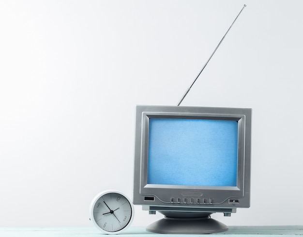 Antenna old-fashioned retro tv receiver and clock on white wall