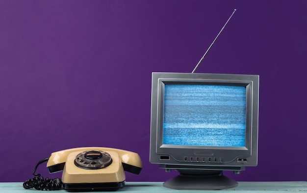 Antenna old-fashioned retro tv receiver and rotary telephone on purple