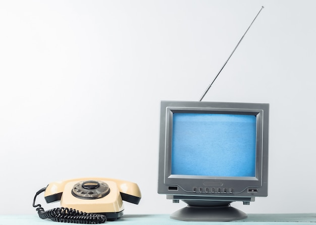 Antenna old-fashioned retro tv receiver and rotary telephone on white wall