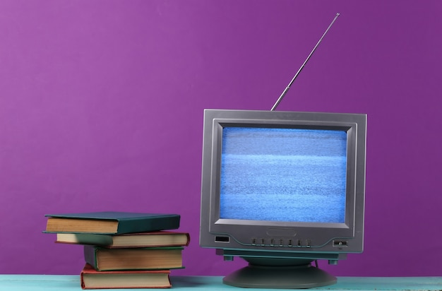 Antenna old-fashioned retro tv receiver and stack of books on purple