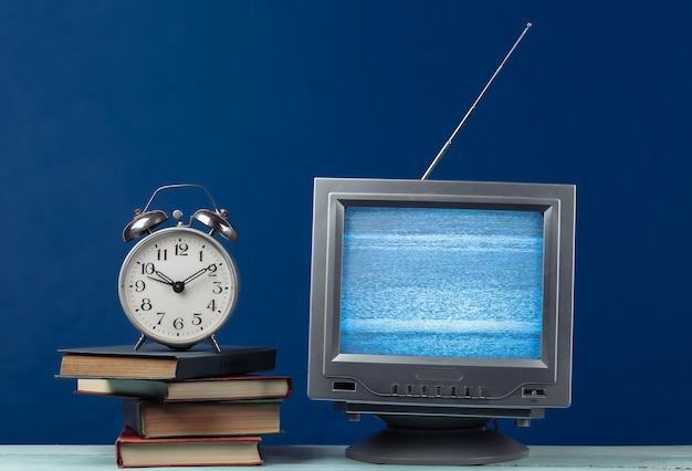 Antenna old-fashioned retro tv receiver and stack of books with alarm clock on classic blue