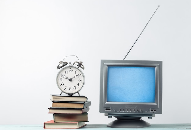 Antenna old-fashioned retro tv receiver and stack of books with alarm clock on white wall