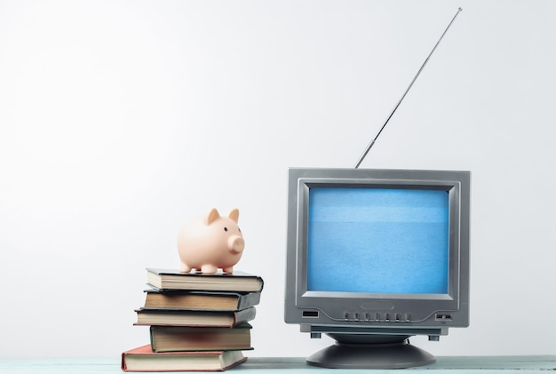 Antenna old-fashioned retro tv receiver and stack of books with piggy bank on white wall