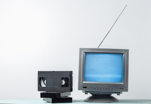 Antenna old-fashioned retro tv receiver and video cassettes on white wall.
