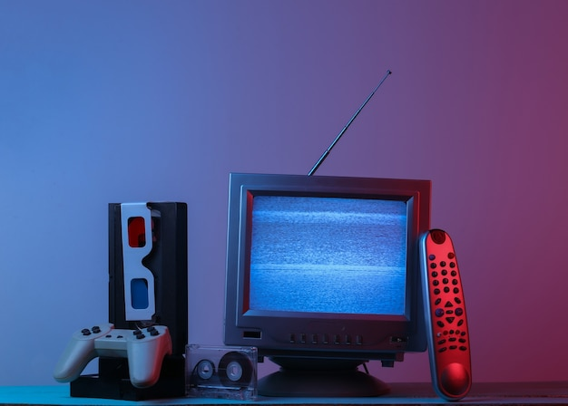 Antenna old-fashioned tv receiver, anaglyph glasses, clock, audio and video cassette, gamepad, remote in pink blue gradient neon light. retro wave