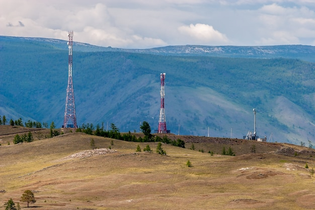 Antennas of cell towers with transmitters standing on the hills in the background of mountains