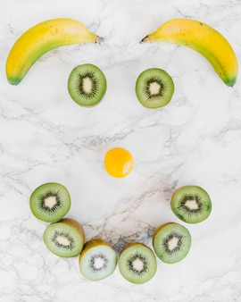 Anthropomorphic face made up of bananas; kiwis and plum fruits on marble