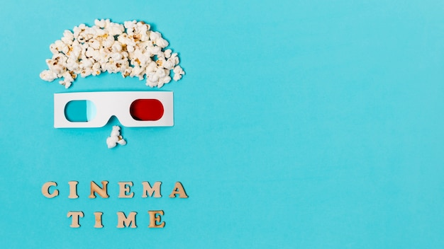 Anthropomorphic face made with popcorns and 3d glasses over the cinema time text