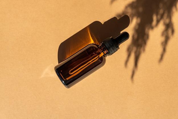 コピースペースのあるベージュの背景に乾燥した耳の葦またはパンパが付いた暗いガラス瓶に入ったアンチエイジングコラーゲンフェイシャルセラム。ナチュラルオーガニックコスメティックビューティーコンセプト