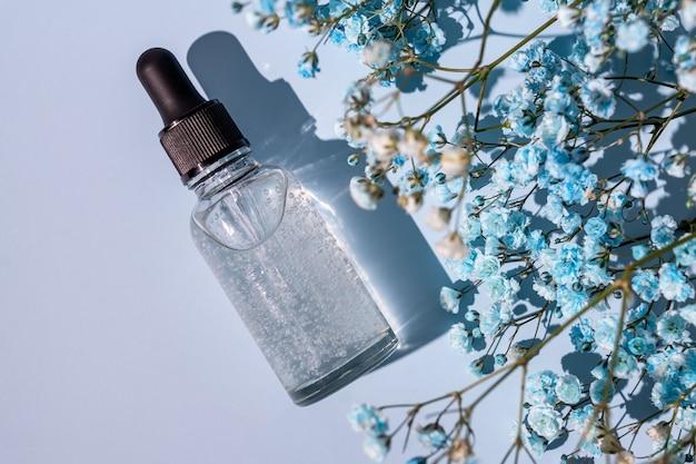 Антивозрастная коллагеновая сыворотка для лица в прозрачной стеклянной бутылке на фоне blye с копией пространства. естественная органическая косметическая концепция красоты.