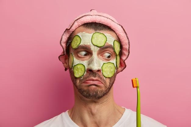 노화 방지 절차 및 치아 관리 개념. 놀란 형태가 이루어지지 않은 유럽 남자의 총을 닫습니다. 화장품 얼굴 마스크를 착용하고 칫솔에 충격을 받았습니다.