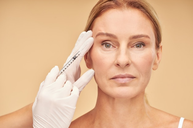 アンチエイジングの手順美容師によるヒアルロン酸注射を受けている美しい成熟した女性
