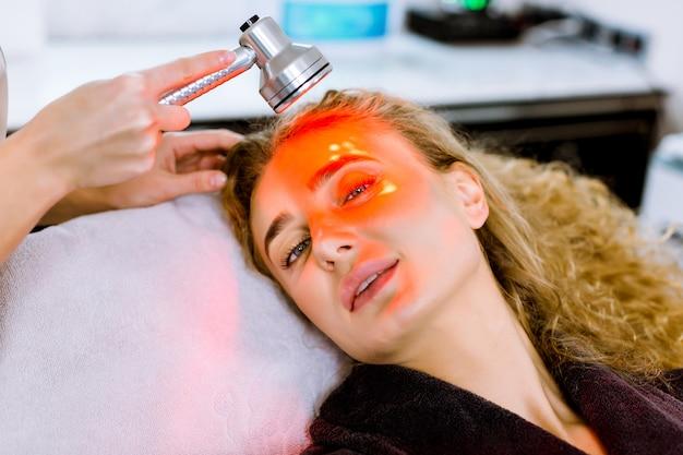 노화 방지 절차. 피부 관리 개념. 현대 화장품 클리닉에서 얼굴 미용 치료를 받고 꽤 금발 여자. 빨간지도 된 가벼운 치료.