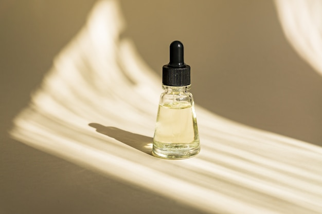 Anti aging serum in glass bottle with dropper on beige wall. facial liquid essential with collagen and peptides.