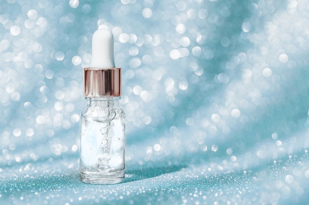 Anti aging serum in glass bottle with dropper on blue shining