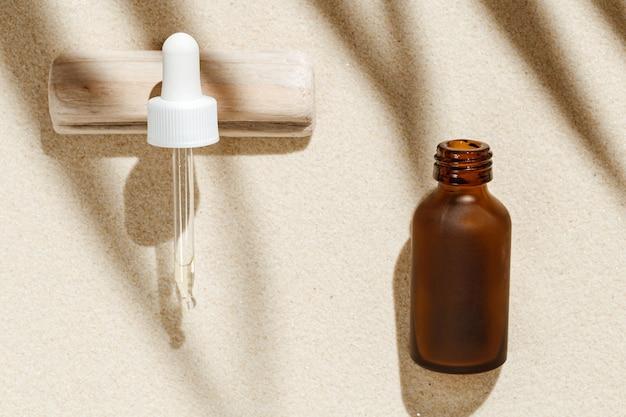 砂の背景にスポイトで暗いガラス瓶にコラーゲンとペプチドを含む老化防止血清
