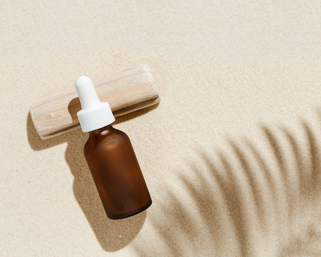 Anti aging serum with collagen and peptides in dark glass bottle with dropper on sandy background