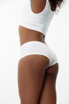 셀룰 라이트 방지 및 마사지. 흰 벽에 슬림 그을린 여성의 등. 잘 관리 된 모양과 피부를 가진 아프리카 계 미국인 모델. 미용, 자기 관리, 체중 감량, 피트니스, 슬리밍 개념.