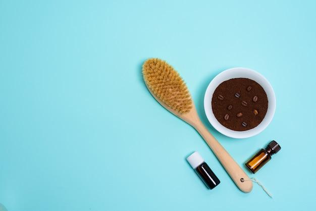Антицеллюлитная сухая массажная щетка для тела, ароматерапевтическое масло, массажер и кофейный скраб на синем фоне