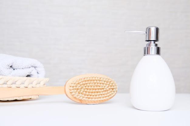 안티 셀룰 라이트 드라이 브러쉬 마사지 개념, 바디 케어 및 셀프 마사지 용 액세서리, 수건 및 크림 복사 공간이있는 욕실.