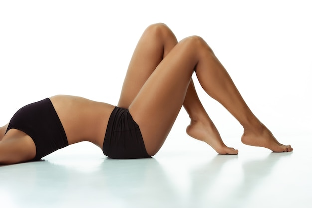 Anti-cellulite and epilation. slim tanned woman's body on white studio background. african-american model with well-kept shape and skin. beauty, self-care, weight loss, fitness, slimming concept.