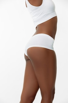 Anti-cellulite and epilation. slim tanned woman's legs on white studio background. african-american model with well-kept shape and skin. beauty, self-care, weight loss, fitness, slimming concept.
