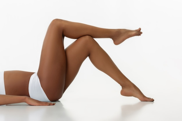 Anti-cellulite and epilation. slim tanned woman's legs on white  wall. african-american model with well-kept shape and skin. beauty, self-care, weight loss, fitness, slimming concept.