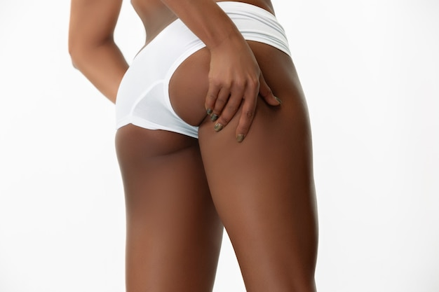 Anti-cellulite and massage. slim tanned woman's back on white studio background. african-american model with well-kept shape and skin. beauty, self-care, weight loss, fitness, slimming concept.