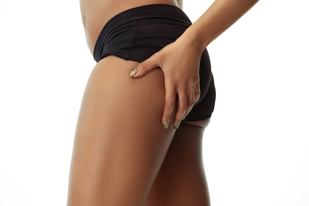 Anti-cellulite. slim tanned woman's body isolated on white studio background. african-american female model with well-kept shape and skin. beauty, self-care, weight loss, fitness, slimming concept.