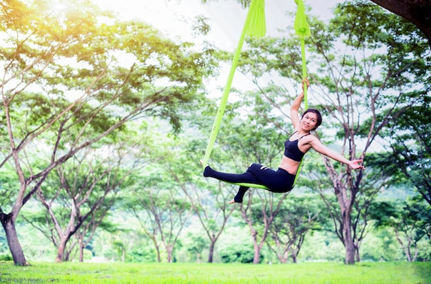 Anti-gravity yoga or aerial yoga at outdoor with public park; acrobatic fly..