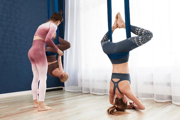 反重力ヨガインストラクター、エアハンモックのトレーニングを監督し、女の子は逆さまにハンモックでヨガのエクササイズをトレーニングします。