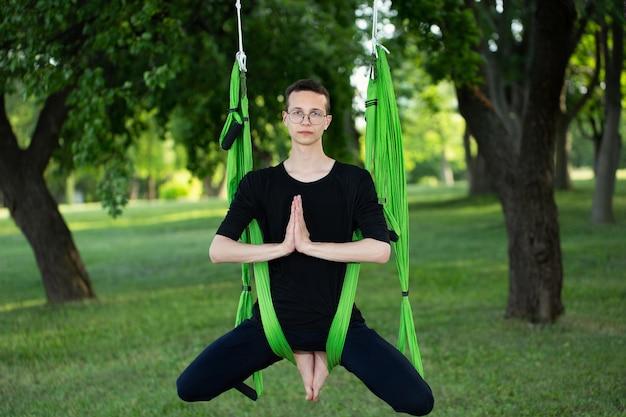 Антигравитационная йога, мужчина делает упражнения йоги в парке