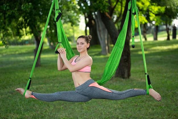 Антигравитационная йога, женщина делает упражнения йоги в парке