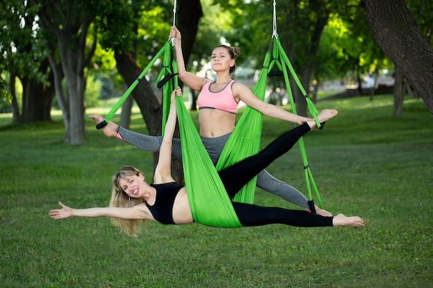 Антигравитационная йога, женщины делают упражнения йоги в парке