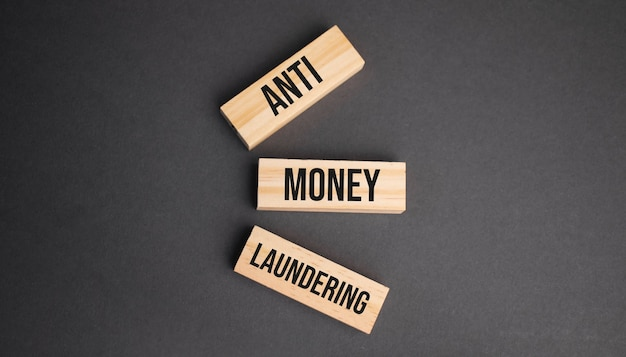 Слово против отмывания денег, написанное на деревянном блоке. объективный текст на столе, концепция.