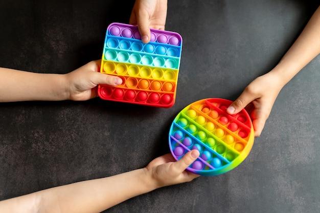 Антистрессовая сенсорная игрушка pop it в детских руках. маленькие счастливые дети делятся и играют с простыми игрушками с ямочками на черном столе.