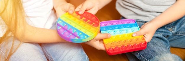 Антистрессовая сенсорная игрушка pop it в детских руках, дети делились игрушками и играли с ними дома
