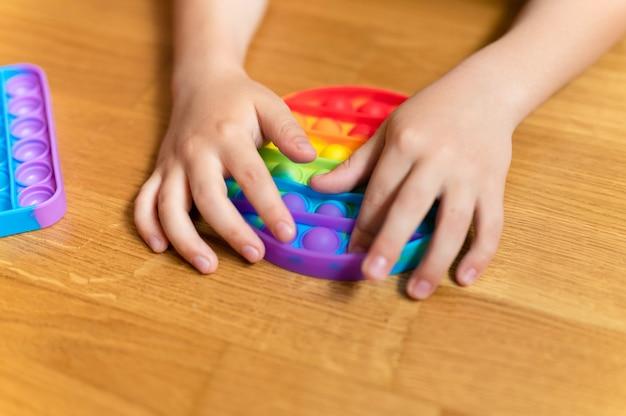 Антистрессовые сенсорные игрушки pop it в детских руках. маленький счастливый мальчик играет с простой игрушкой с ямочками на щеках дома.