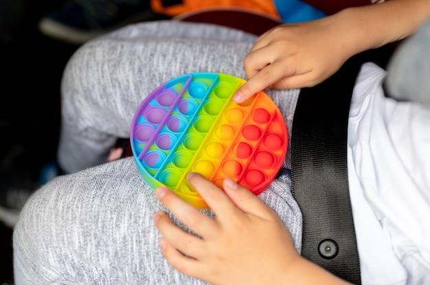 Антистрессовые сенсорные игрушки pop it в детских руках. маленький счастливый мальчик играет с простой игрушкой с ямочками в машине.