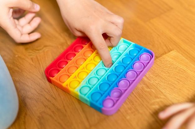 Антистрессовые сенсорные игрушки pop it в детских руках. маленькая счастливая девочка играет с простой игрушкой на щеках дома.