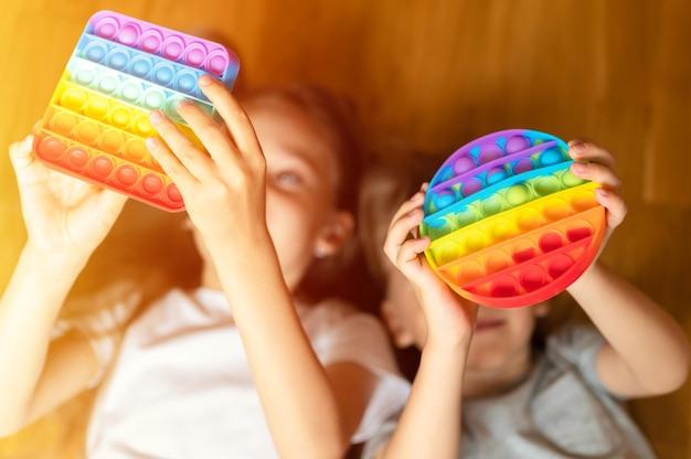 Антистрессовые сенсорные игрушки pop it в детских руках. маленькие счастливые дети играют с простой игрушкой с ямочками на щеках. . вспышка