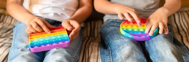 Антистрессовые сенсорные игрушки pop it в детских руках. маленькие счастливые дети играют с простой игрушкой с ямочками на щеках. малыши держат и играют в цвет радуги, тренд 2021 года. знамя