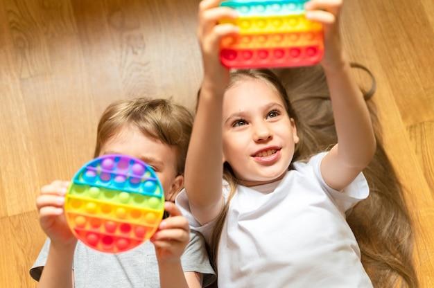 Антистрессовые сенсорные игрушки pop it в детских руках. маленькие счастливые дети играют с простой игрушкой с ямочками на щеках.
