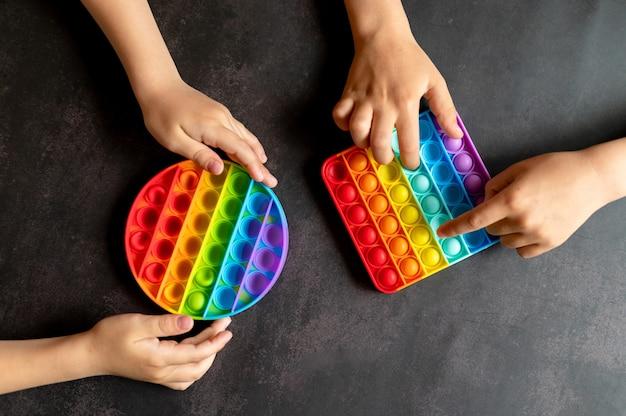 Антистрессовые сенсорные игрушки pop it в детских руках. маленькие счастливые дети играют с простой игрушкой с ямочками на черном столе.