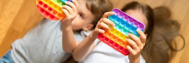 Антистрессовые сенсорные игрушки pop it в детских руках. маленькие счастливые дети играют с игрушкой