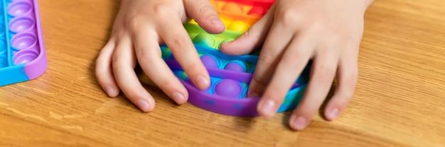 Антистресс сенсорные игрушки pop it в детских руках маленький счастливый мальчик играет с игрушкой