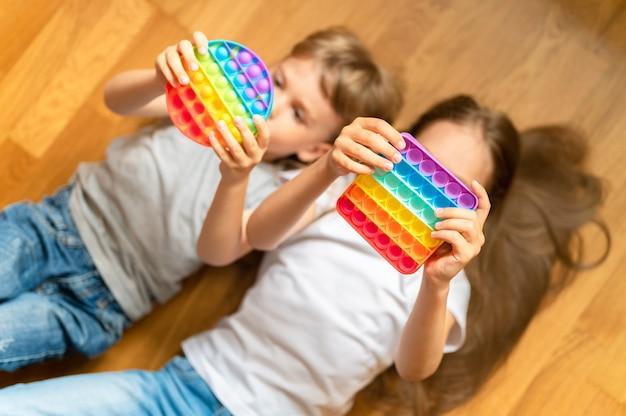 Антистресс сенсорные игрушки pop it в детских руках маленькие счастливые дети играют с игрушкой дома
