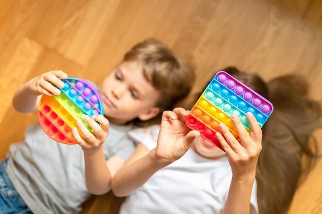 Антистресс сенсорные игрушки pop it в детских руках маленькие счастливые дети играют с игрушкой